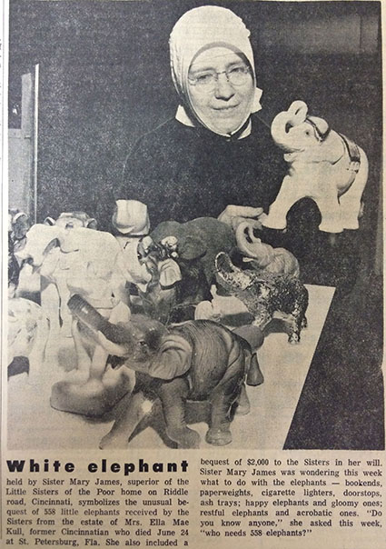 Sister Mary James, then-Superior of the Little Sisters of the Poor Cincinnati, poses with a parade of elephant figurines donated to the order in 1965. (CT File)