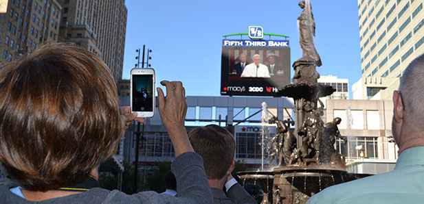 Onlookers at Cincinnati's Fountain Square film Pope Francis with their mobile devices. (CT Photo/John Stegeman)