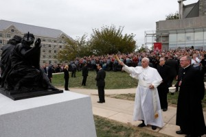 """Pope Francis blesses a sculpture during a brief stop at St. Joseph's University in Philadelphia Sept. 27. The sculpture commemorates the 50th anniversary of """"Nostra Aetate,"""" the Second Vatican Council Declaration on the Relationship of the Church to Non-Christian Religions.  (CNS photo/Paul Haring)"""
