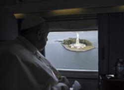 Pope Francis looks out at the Statue of Liberty while flying over New York Harbor on his way from New York to Philadelphia Sept. 26. (CNS photo/L'Osservatore Romano via Reuters)
