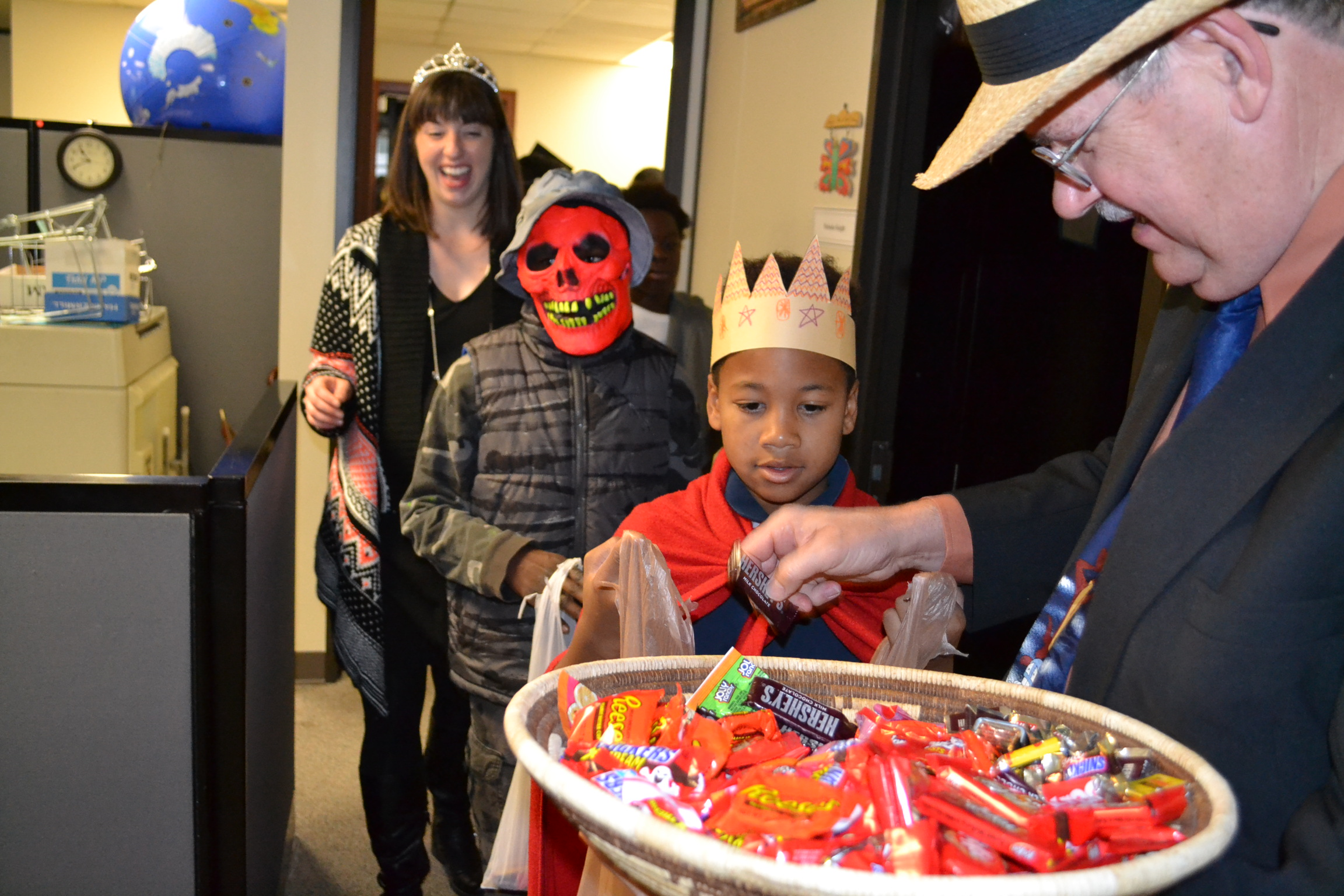 Students from St. Francis Seraph School get candy from Mike Gable of the Archdiocese of Cincinnati Mission Office on Oct. 30. (CT Photo/John Stegeman)