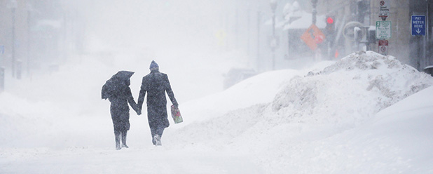 A couple walks hand-in-hand through the snow during a winter blizzard in Boston. (CNS photo/Brian Snyder, Reuters)