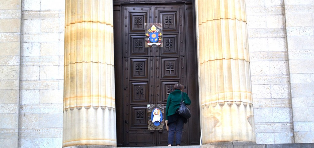 A woman examines the Holy Door of Mercy at the Cathedral of St. Peter in Chains in downtown Cincinnati. The holy door was sealed in a Nov. 1 ceremony. It will be opened in a ceremony by Cincinnati Archbishop Dennis M. Schnurr at the 11 a.m. Sunday Mass on Dec. 13. (CT Photo/John Stegeman)
