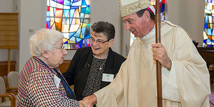 Sister of Notre Dame de Namur Mary Alice Weber, left, celebrating 80 years in her religious community, is greeted by Archbishop Dennis M. Schnurr as Ursuline Sister Lucia Castellini looks on. (CT Photo/Colleen Kelley)