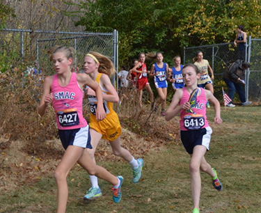 SMAC runners Emma Holly (carrying shoe) runs out of the woods.  Also pictured is her teammate Kirsten Thomas. (Courtesy Photo)