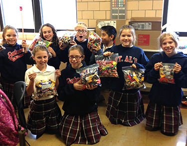 St. Al's students hold bags of candy they contributed to the effort. (Courtesy Photo)