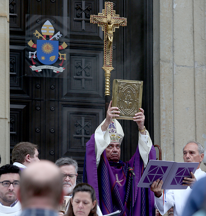 Archbishop of Cincinnati Dennis M. Schnurr holds the the Gospels aloft before opening the Holy Door of Mercy Dec. 13 at the Cathedral of St. Peter in Chains. (CT Photo/E.L. Hubbard)