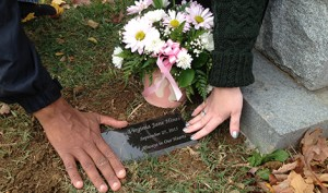 "Mary McCarthy Hines and her husband, Charles, touch the grave of their stillborn daughter, Virginia, in late October. ""A m.o.m.s. peace"" helped order and install a grave marker for Virginia and honor her life through a remembrance program. (CNS photo/courtesy Kara Palladino)"