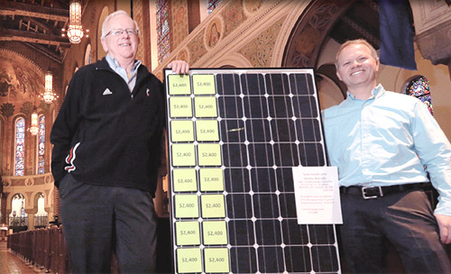 Father Al Hirt, left, holds one of the solar panels that will provide energy to light the campus from church, to parish center, to maintenance garage, to parking lot. (CT Photo/E.L. Hubbard)