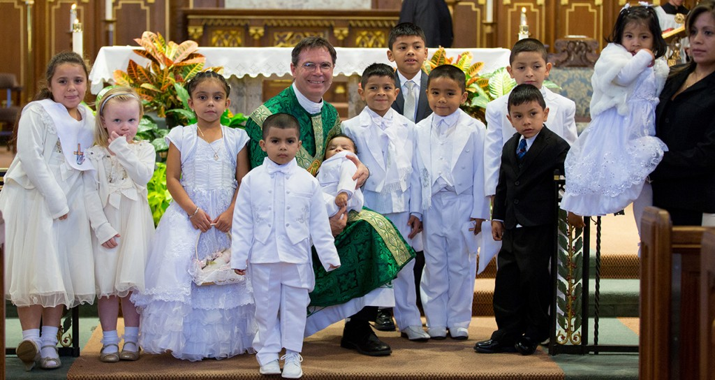 Father Jamie Weber, pastor of St. Cecilia, poses for a photo with a group of recently baptized students. (Courtesy Photo)