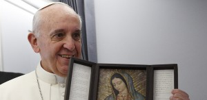 Pope Francis holds an image of Our Lady of Guadalupe aboard the papal flight to Brazil in this July 22, 2013, file photo. The pope is deeply devoted to Mary and visited the image of Guadalupe while in Mexico last week. (CNS photo/Paul Haring)