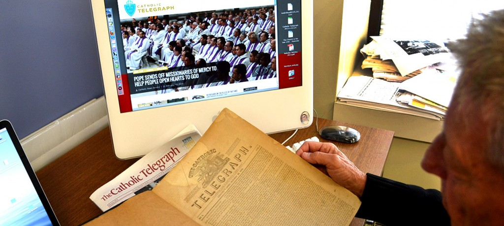 A visitor to The Catholic Telegraph offices compares the Oct. 22, 1831 edition of the newspaper to the current edition and website during Catholic Press Month 2016. (CT Photo/John Stegeman)
