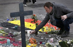 A man places flowers on a street memorial March 23 following bomb attacks in Brussels. Three nearly simultaneous attacks March 22 claimed the lives of dozens and injured more than 200. (CNS photo/Francois Lenoir, Reuters)