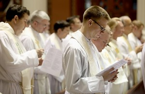 Father Ethan Moore, right, and other priests, sing during the Chrism Mass at the Cathedral of Saint Peter in Chains in Cincinnati Tuesday, March 22, 2016. (CT Photo/E.L. Hubbard)