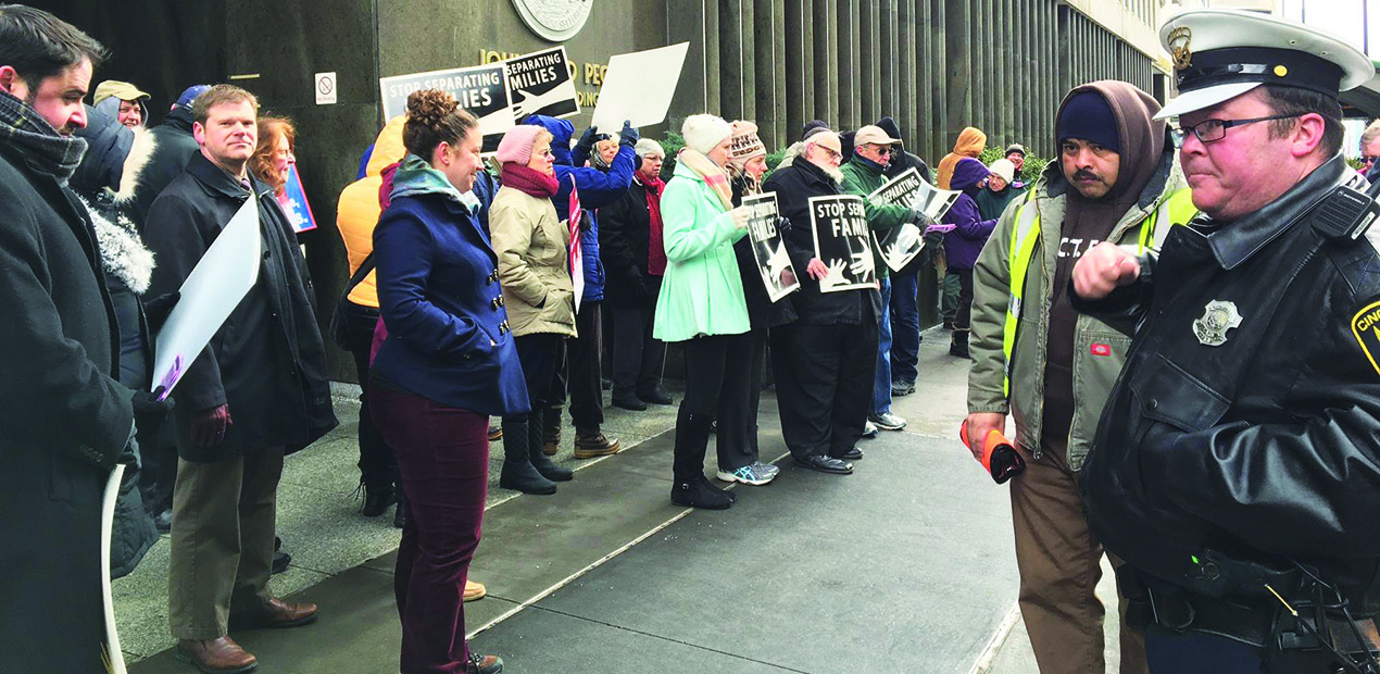 A Cincinnati Police officer looks on as a multi-faith group rallied in front of the John Weld Peck federal building on Ash Wednesday to bring awareness to the plight of immigrants coming to the United States to escape violence in their native lands. (Courtesy Photo)