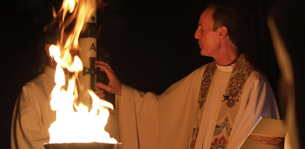 Father Robert Smith, pastor of St. James Parish in Setauket, N.Y., marks the paschal candle at the beginning of the Easter Vigil at his church April 19, 2014. (CNS photo/Gregory A. Shemitz, Long Island Catholic)