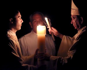 The Most Reverend Dennis M. Schnurr, Archbishop of Cincinnati, lights a candle with the flame of the Easter Candle during the Easter Night Vigil in the Holy Night on Holy Saturday, March 26, 2016, at the Cathedral of Saint Peter in Chains in Cincinnati.