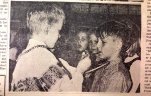 "Steve Vogel, right, receives an unconsecrated host from ""priest"" Clark Monroe during a communion demonstration in preparation for the students' first communion in 1966. (CT File)"