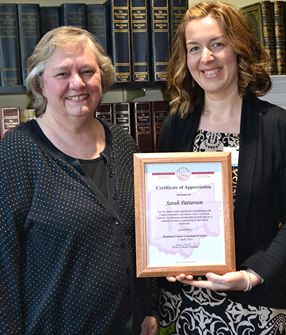 Archdiocese of Cincinnati Archivist Sarah Patterson, right, and volunteer Julie Ross were honored by the Hamilton County Genealogical Society for their work at the achieves. Each received a certificate though only Patterson's is seen here. (CT Photo/John Stegeman)