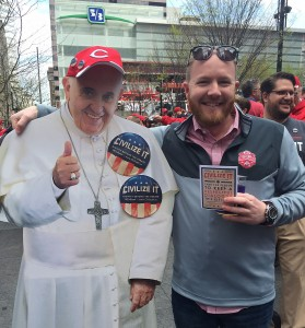 "A man holding a card promoting the Archdiocese of Cincinnati's ""Civilize It'"" campaign stands with a cutout of Pope Francis April 4 during festivities before the Cincinnati Reds season-opening game. The campaign is designed to encourage people to be respectful of the views of others during the electoral campaigns. (CNS photo/Mimi London, Archdiocese of Cincinnati)"