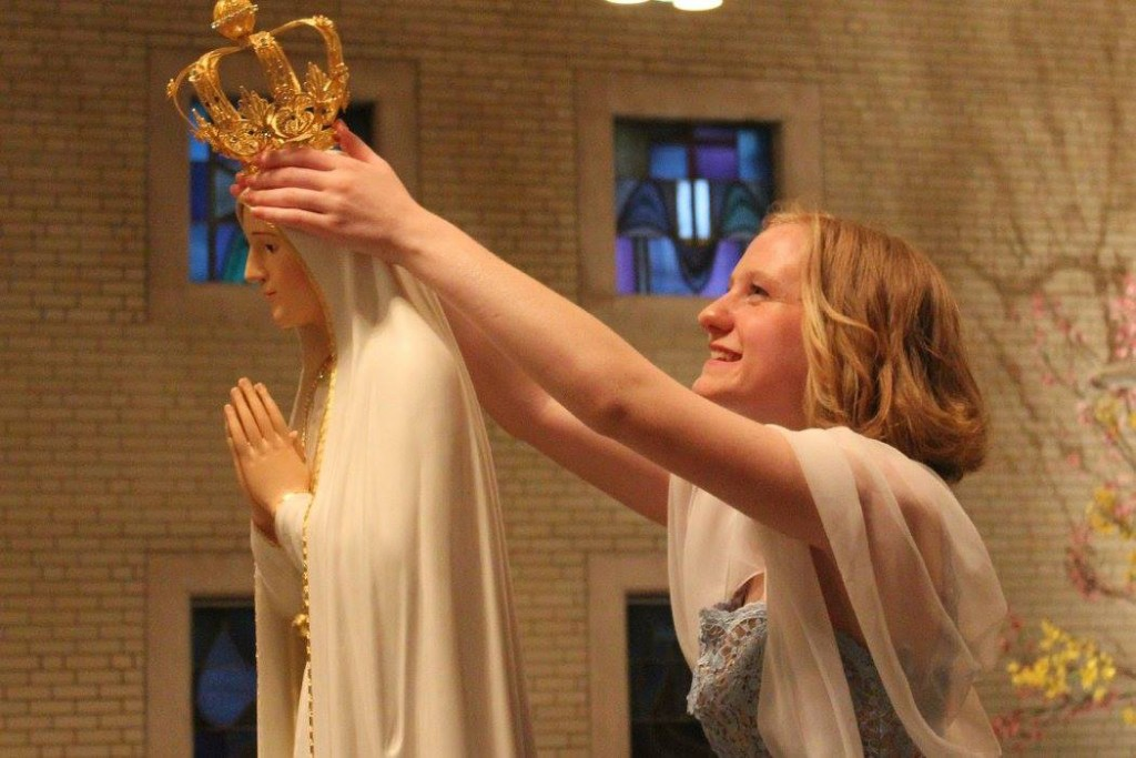 A St. Gertrude student crowns a statue of the Blessed Virgin during May Crowning 2016. (Courtesy Photo)