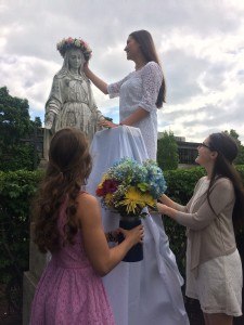 Lehman Catholic student Diana Gibson crowns Mary as Emma Simpson (right bottom) and Cassidy Hemm (left bottom) bring gifts of flowers to the Holy Mother during the recent May Crowning ceremony held at Lehman Catholic High School. (Courtesy Photo)