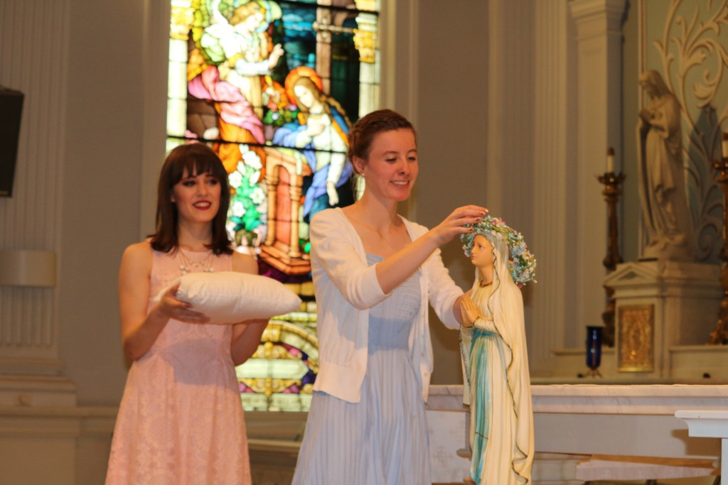Saint Ursula Academy seniors Gabrielle Silvestri (left) and Sarah Tippenhauer (right) crowned a statue of the Blessed Mother Mary during a May Crowning ceremony in the Saint Ursula Academy chapel on April 29.