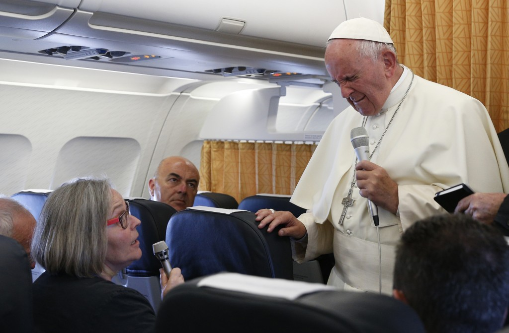 Pope Francis closes his eyes as he reacts to a question from Cindy Wooden, Catholic News Service Rome bureau chief, aboard his flight from Yerevan, Armenia, to Rome June 26. The pope reacted as Wooden mentioned the June 12 shooting that killed 49 at a nightclub in Orlando, Fla.