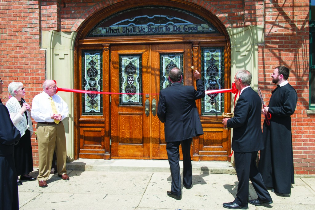 Archbishop Dennis M. Schnurr blesses the front door of the new residence of the St. Philip Neri Community in Formation at 118 E. 12th Street in Over-the-Rhine. At far right is Father Jon-Paul Bevak, moderator of the Oratory, holding ceremonial scissors that would be used to cut the ribbon to officially open the facility. The ceremony took place April 18. (CT Photo/Colleen Kelly)