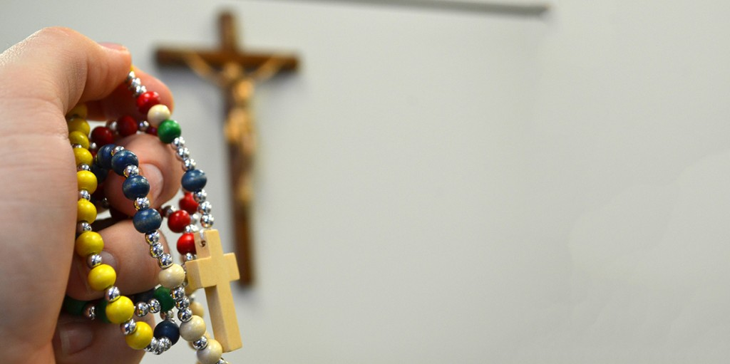 A hand holds a rainbow-colored rosary in front of a crucifix. Rainbow imagery is often associated with LGBTQ movements. Courage International, an apostolate for Catholics with homosexual desires, uses only a crucifix and the group's name as a logo. (CT Photo/John Stegeman)