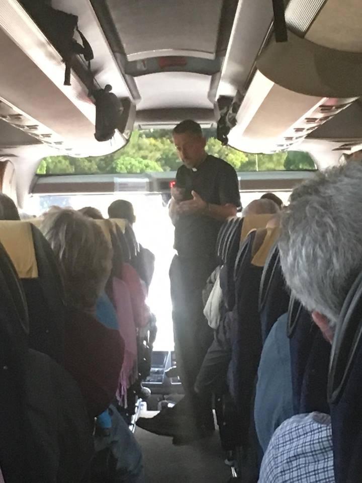 Pilgrims play stump the Priest on the bus to their next destination. (Courtesy Photo)