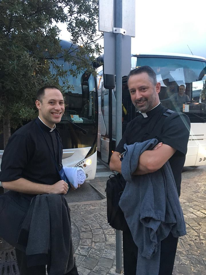 Fr. Timothy Fahey of the Archdiocese of Cincinnati and Fr. Rich Kunst of the Diocese of Duluth converse before boarding to the next destination. (Courtesy Photo)