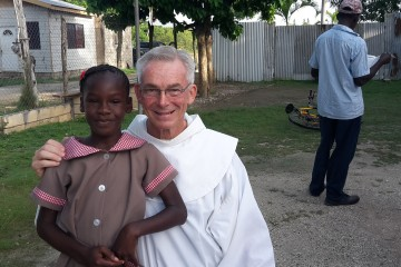 Franciscan Father Jim Bok poses with a Jamaican child. (Courtesy Photo)