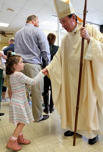Sophie Kellogg, 5, shakes hands with Archbishop Dennis Schnurr after the Queen of Peace Catholic Church 75th Anniversary Mass on Sunday, October 2, 2016, in Millville, Ohio. (CT Photo/E.L. Hubbard)