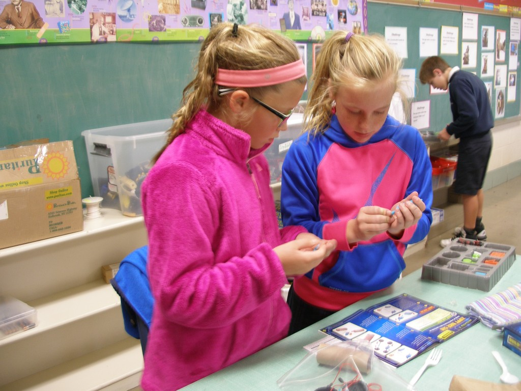 Our Lady of Lourdes students Bella Maxfield and Emily Smith create a car using a circuitry kit, cardboard tube and assorted items. (Courtesy Photo)