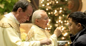 The Catholic Telegraph/E.L. Hubbard Archbishop Dennis Schnurr and Rev. Louis Gasparini give Holy Communion during Day of Prayer for World Justice and Peace at Saint Peter in Chains Cathedral in Cincinnati Wednesday, January 1, 2014.