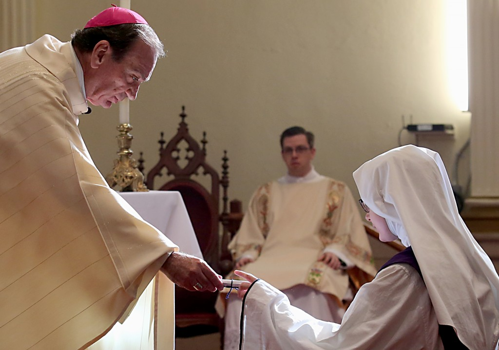 Archbishop Dennis Schnurr hands a scroll to Sister Antonietta Maria as she accepts her new name during Holy Mass to celebrate the erection of the Children of Mary Motherhouse at the Our Lady of the Holy Spirit Center in Norwood Monday, Nov. 21, 2016. (CT Photo/E.L. Hubbard)
