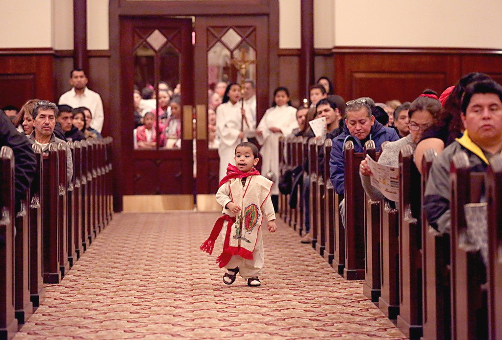 A young boy, dressed as Saint Juan Diego, runs down the aisle during the Feast of Our Lady of Guadalupe at St. Julie Billiart parish in Hamilton Sunday, Dec. 11, 2016. The Day of Prayer was to focus on the plight of refugees and migrants across the United States. (CT Photo/E.L. Hubbard)