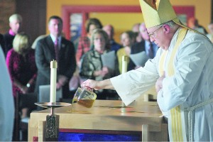Bishop Binzer consecrates the altar with blessed oil. (CT Photo/ Jeff Unroe)