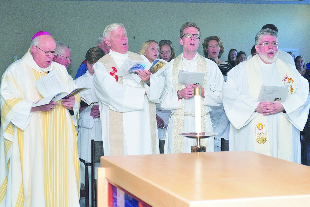 Bishop Joseph R. Binzer sings with Fathers Dave Brinkmoller, Ethan Moore and Steve DeSantos. (CT Photo/Jeff Unroe)
