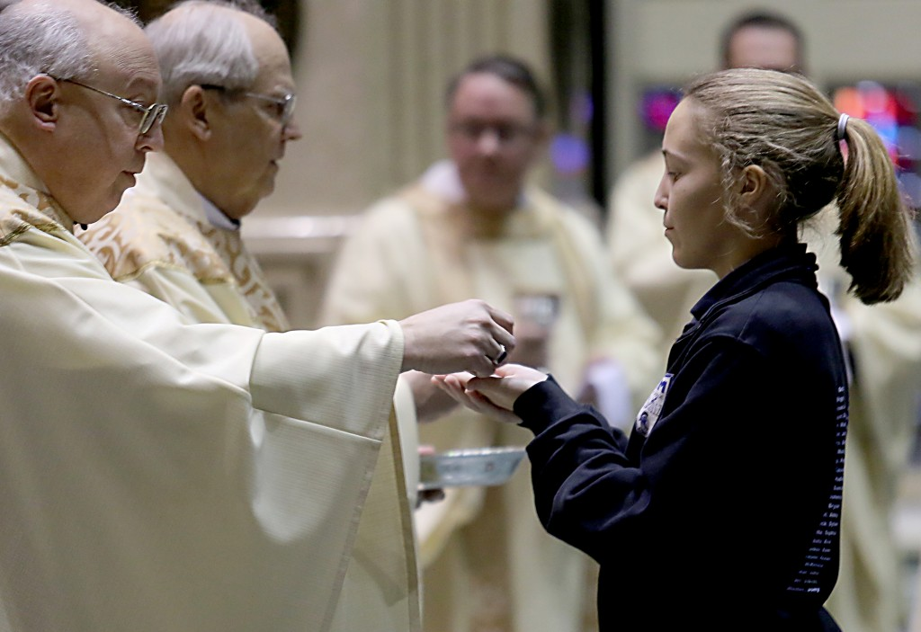 Auxiliary Bishop Most Reverend Joseph Binzer offers a student Communion during the Catholic Schools Week Mass at the Cathedral of Saint Peter in Chains in Cincinnati Tuesday, Jan. 31, 2017. (CT Photo/E.L. Hubbard)