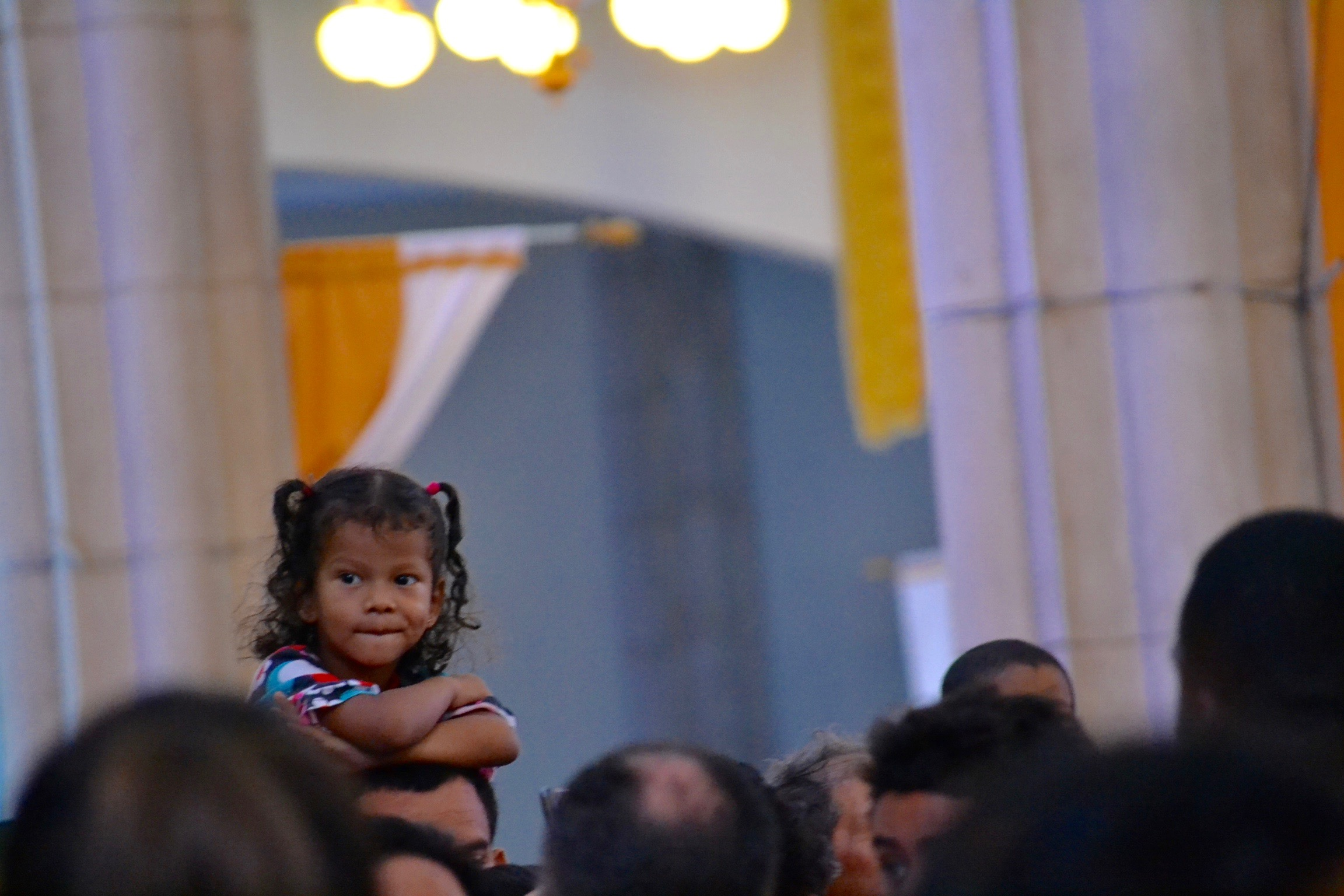 Sitting on a relative's shoulders, a Honduran girl watches Mass (CT/Photo by Gail Finke)
