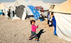 A displaced Iraqi child walks outside tents Dec. 9 at the Hassan Sham camp near Mosul. As Christians in the Middle East look back on 2016, they wonder if there will be much to celebrate amid mounting challenges, particularly for those displaced by conflicts in Iraq and Syria. (CNS photo/Ahmed Jadallah, Reuters)