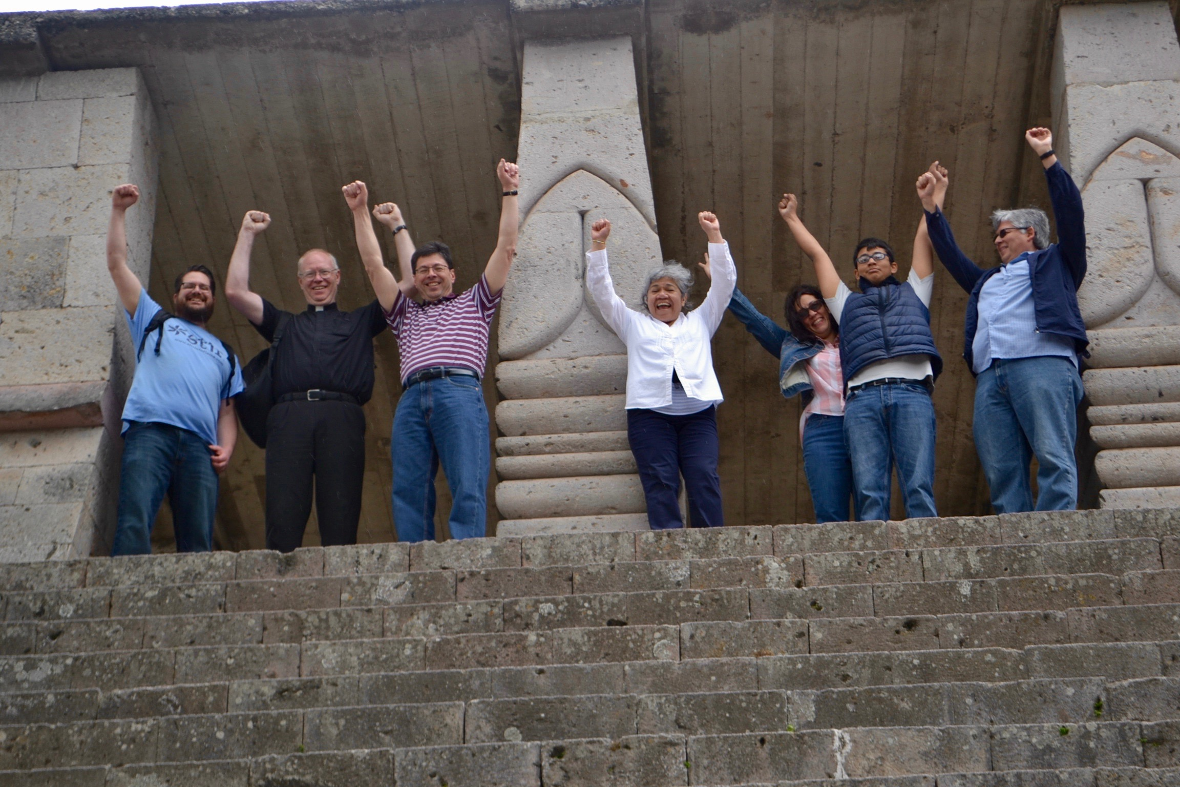 Some of the Archdiocese's visitors and Honduran hosts pose like Rocky at a replica Mayan temple, after climbing dozens of steep steps (CT/Photo by Gail Finke)