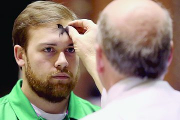 Mike Wolf marks a parishioner's forehead with the sign of a cross during Ash Wednesday services at St. Peter in Chains Cathedral in Cincinnati Wednesday, Mar. 1, 2017. (CT PHOTO/E.L. HUBBARD)
