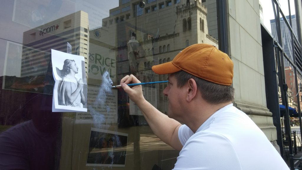 Michael Glass a St. Mary Greenville Ohio parishioner begins his painting at the display window.