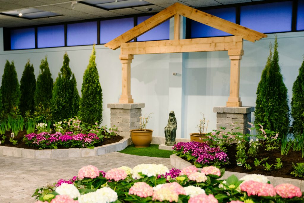 """A statue of St Joseph once sold by John Stokes sits framed by Arborvitae bushes and Cineraria, Siberian Iris, meadow sage (""""Mary's Shawl"""") and snowdrop (Anemone sylvestris, """"Flower of the Field""""). (COURTESY PHOTOS/BRIANA SNYDER)"""