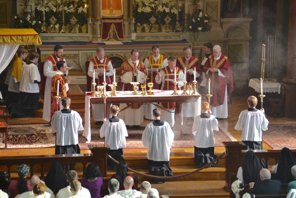 Oratory Father Mario Aviles (reading) with some of the concelebrating priests, Deacon Duy Nguyen, and servers. Left to right: Father John-Paul Bevak of Old St. Mary's; Father Felix Selden, representing Rome; Archbishop Dennis Schnurr; Fathers Adrian Hilton and Lawrnce Juarez of Old St. Mary's; and homilist  Msgr. Frank Lane. (CT Photo/Gail Finke)