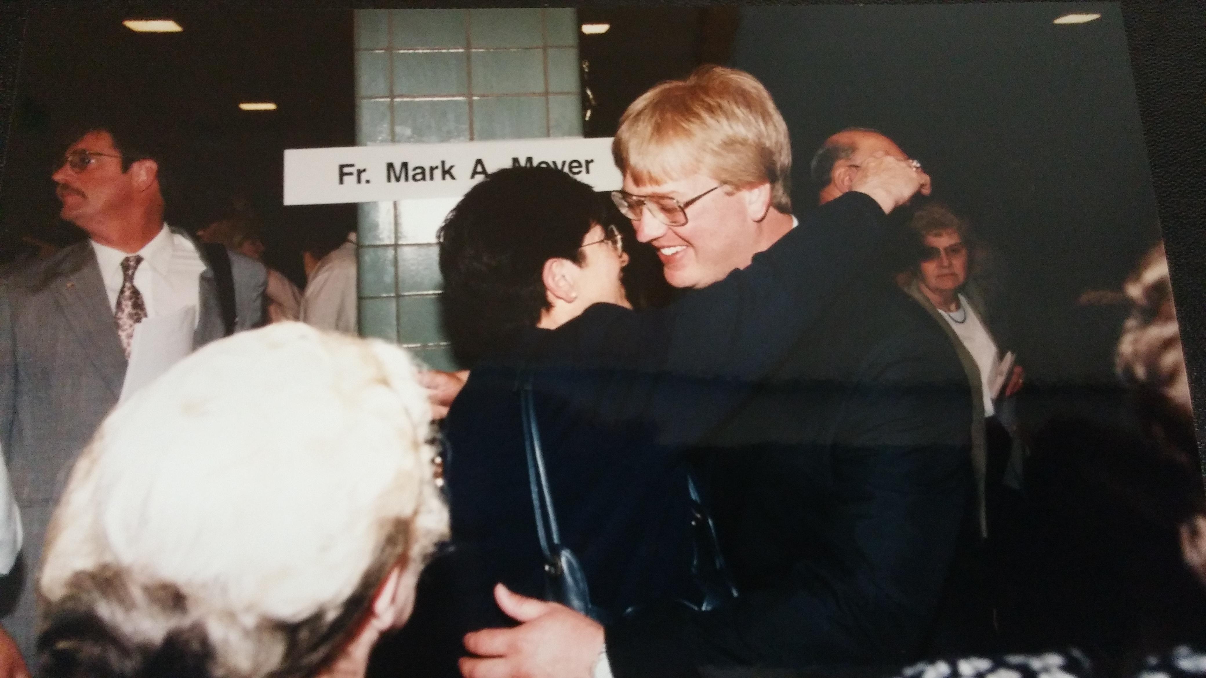 Fr. Mark Meyer receives congratulatory hugs.