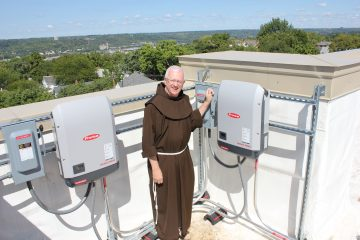 Franciscan Father Al Hirt, pastor of St. Monica-St. George Parish Newman Center, prepares to throw the switch on the inverters that convert solar power DC to alternating current on the roof of the parish center recently. (Courtesy Photo)